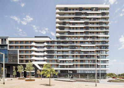 El volumen más bajo, de 7 alturas, se conecta en forma de puente de 16 m de luz al edificio anexto, donde se ubica el terciario, y otro vlument de 14 plantas alberga las viviendas