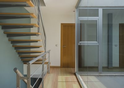Escaleras de madera natural que aportan dinamismo a la estancia principal