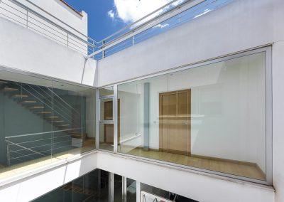 Amplios ventanales dispuestos por toda la vertical del patio